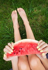 Young girl with watermelon sitting on the grass