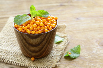 fresh ripe organic sea buckthorn berries in a wooden mug