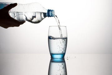 Hand Pouring Water In Water Glass