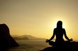 Fototapety Yoga lotus position silhouette on seaside at sunrise