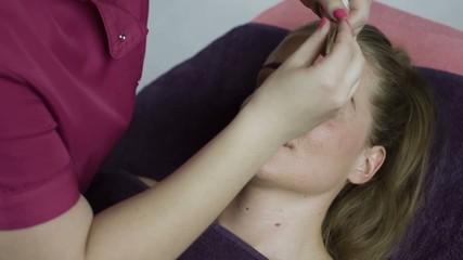 Woman getting tweezing eyebrow by beautician