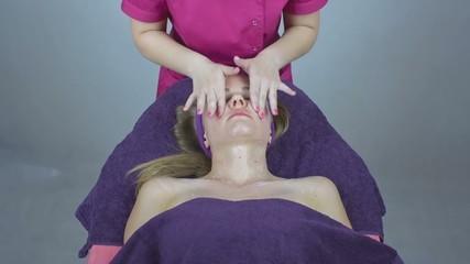 Beautician giving pretty woman face massage in beauty salon
