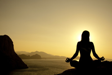 Yoga lotus position silhouette on seaside at sunrise