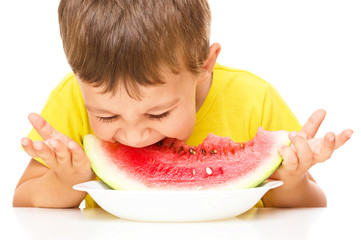 Little boy is eating watermelon