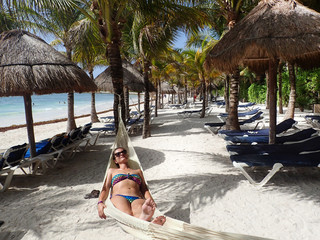 woman lying in a hammock on the beach