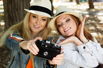 Two teenagers girl taking selfe with camera
