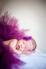 A sleeping baby girl wearing purple yarn soft focus