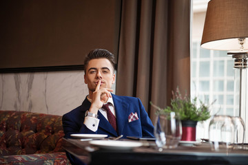Successful businessman sitting at the table of the restaurant
