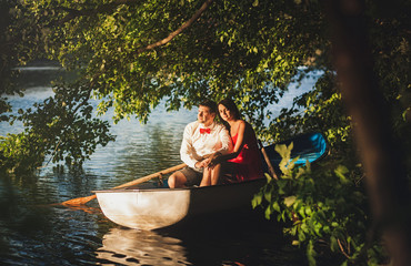 Romantic couple sitting in a boat in the shade of the trees
