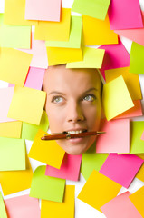 Woman with many reminder notes and pen in the mouth