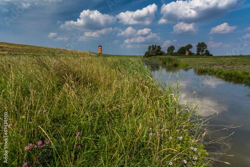 canvas print picture Ostfriesische Landschaft mit dem Pilsumer Leuchtturm