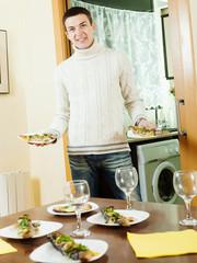 Handsome guy serving festive table