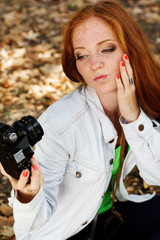 Nice girl photographer taking selfe in autumn park