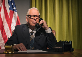 Big boss president wearing glasses calling behind desk with amer