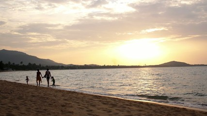Happy Family Walking on Beach at Sunset. Slow Motion.