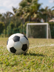 soccer ball in grass on green field near five-a-side goal
