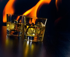 glasses of whiskey with ice cubes in front of the flame