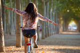 Pretty young girl riding bike in a forest. poster