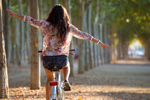 Plexiglas Bossen Pretty young girl riding bike in a forest.