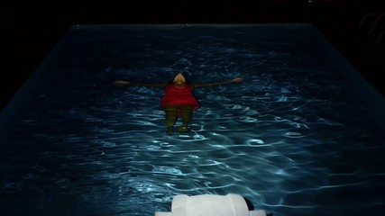 Young Drowned Woman Lying in Pool Water at Night. Slow Motion.