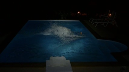 Female Falling into the Swimming Pool at Night. Slow Motion.