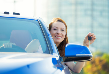 Happy, smiling woman, buyer sitting in her new car showing keys