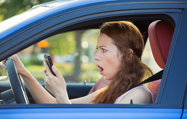 Sressed woman driving in car checking smart phone, bad habits