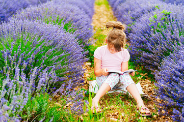 Adorable little girl reading a book in a lavender field
