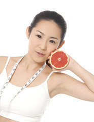 A picture of a young fit woman with slice grapefruit