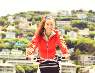 Happy woman riding on bike on a summer day, Sausalito town