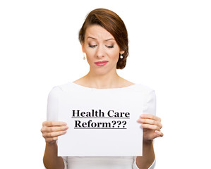 Skeptical woman holding sign health care reform?