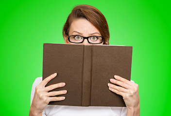 Woman with glasses hiding her face behind book