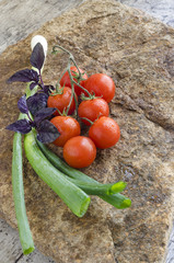 Fresh vegetables: cherry tomatoes, onion and basil on a stone