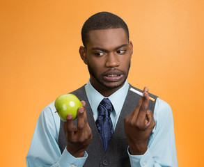 Man craving cigarette versus green apple on orange background