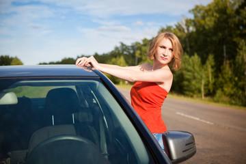 Красивая девушка в красной одежде возле машины на природе