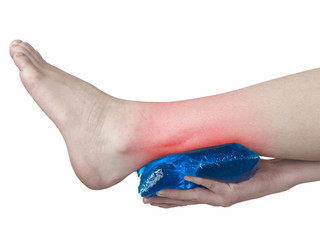 Acute pain in ankle. Woman holding hand to spot of ankle-aches.