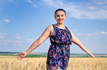 Woman standing enjoying the sun in a wheat field