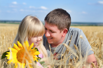 Father playing with his daughter in a wheat field