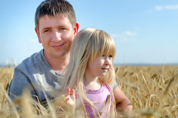 Cute little girl with her father in a wheat field