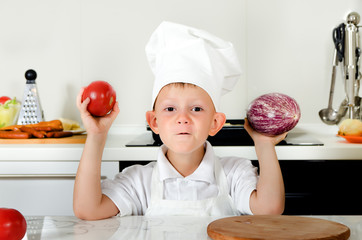Playful little boy in a chefs uniform