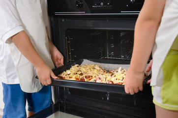 Two children placing homemade pizzas in the oven