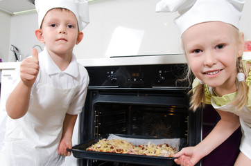 Happy excited young children with homemade pizza