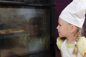 Girl Wearing Chef Hat Looking into Oven at Food