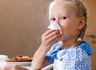 Pretty little girl wiping her mouth with a napkin