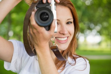 Pretty redhead taking a photo in the park