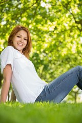 Pretty redhead relaxing in the park smiling at camera