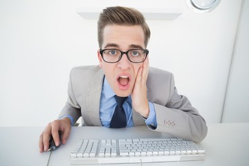 Shocked businessman working on computer
