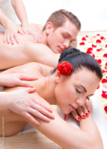 canvas print picture Couple lying  in a spa salon enjoying back massage.