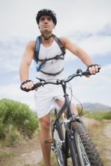 Athletic young man mountain biking