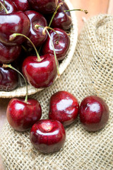 Fresh cherries in bowl on table